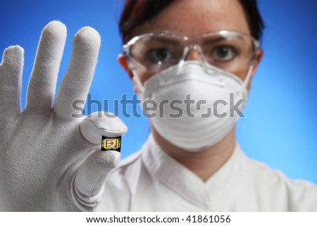 Young beautiful woman in gloves hold microchip(focus on microchip)