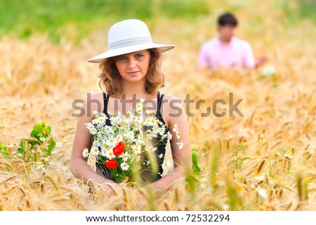 Young beautiful woman in golden wheat field with bouquet of chamomiles