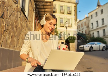Young beautiful woman in headphones with laptop sitting on the steps outdoor, sunset summer city background. Business, study, freelance, recreation and leisure, modern technology concept stock photo