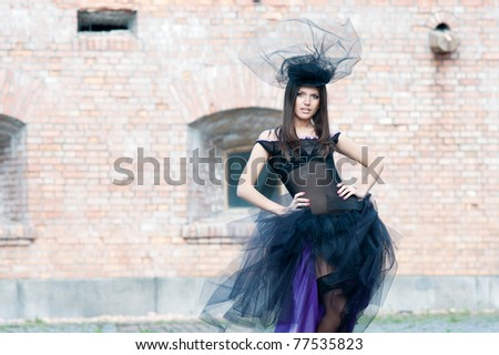Young beautiful woman in incredible dress and hat