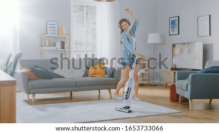Young Beautiful Woman in Jeans Shirt and Shorts is Listening to Music on Her Headpones, Dancing and Vacuum Cleaning a Carpet in a Cozy Room at Home. She Uses a Cordless Vacuum. She's Happy and Joyful.