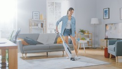 Young Beautiful Woman in Jeans Shirt and Shorts is Vacuum Cleaning a Carpet in a Bright Cozy Room at Home. She Uses a Modern Cordless Vacuum. She's Happy and Cheerful.
