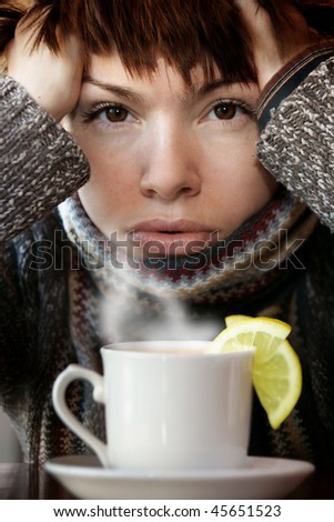 young beautiful woman in knitted scarf,  with the cup of hot tea