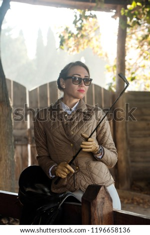 Young beautiful woman in leather gloves at stable.