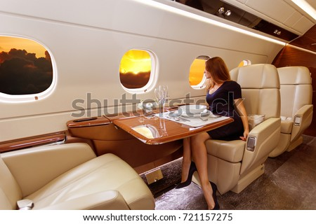 young beautiful woman in Luxury interior in bright colors of genuine leather in the business jet, sky and rays of sunset through the porthole ストックフォト ©