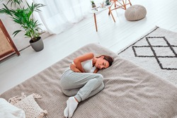 Young beautiful woman in painful expression holding her belly suffering menstrual period pain lying sad on home couch having tummy cramp in female health concept. Top view.