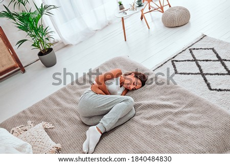 Young beautiful woman in painful expression holding her belly suffering menstrual period pain lying sad on home couch having tummy cramp in female health concept. Top view. Stock photo ©