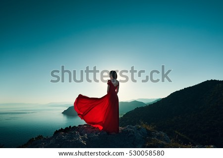 Young beautiful woman in red dress looking to mountains sea. Girl on the nature on blue sky background. Fashion photo #530058580