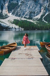 young beautiful woman in red dress walking by wooden pier at mountain lake