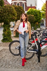Young beautiful woman in red high heel shoes, blue denim jeans pants and teddy jacket coat posing on street bicycle rental parking background in European city