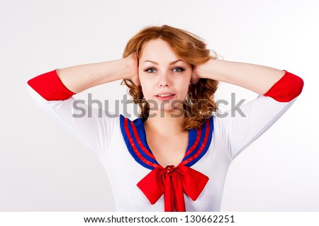 "Young beautiful woman in sailor costume with ""no evil hear"" gesture at white background"