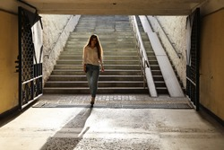 Young beautiful woman in shirt and jeans walked down into the pedestrian underpass. She smiles and is not afraid of the deserted tunnel. Concept of hindsight, danger and defenseless