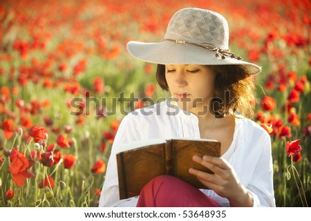 Young beautiful woman in spring writing in field