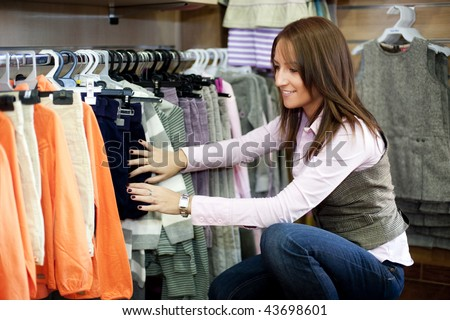 Young beautiful woman in store buying baby clothes