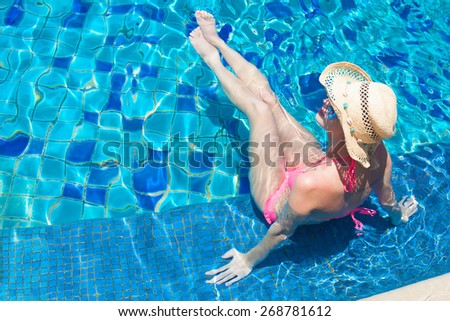 young beautiful woman in straw hat relaxing in spa pool