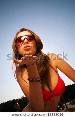 Young beautiful woman in sunglasses blow a kiss to you.