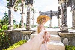 Young beautiful woman in Taman Ujung water palace, Bali island, Indonesia - Travel blogger exploring Water Palace in Bali