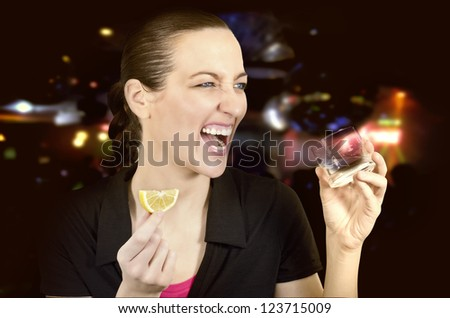 Young beautiful woman in the club drinking alcohol with lime
