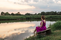 Young beautiful woman in the lilac evening dress with nice hairstyle and makeup. Girl enjoys the sunset reflected in the lake. View from the back. Wedding guest look. Bridesmaid outfit. Belarus, Brest