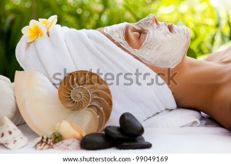 Young beautiful woman in tropical spa making face mask treatment