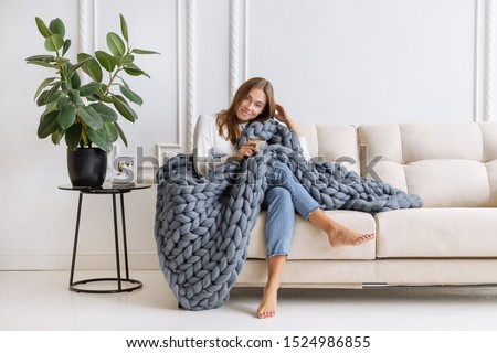 Young beautiful woman in warm chunky knitted blanket at home. Model fashion shooting. Autumn, winter season. Cozy winter style.   Сток-фото ©