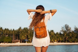 young beautiful woman in white dress on summer vacation, bohemian style, tropical beach, view from back, leather backpack, traveler, freedom spirit