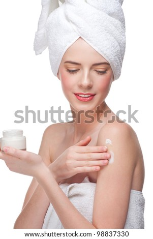 Young beautiful woman in white towel applying moisturizing cream on her shoulder. Isolated on white background