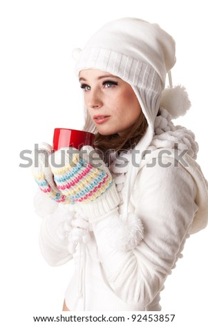 Young beautiful woman in winter warm clothes with red cup on a white background.