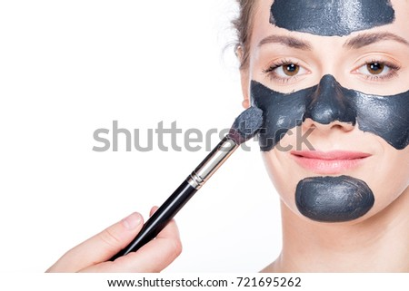 Young beautiful woman is having a black charcoal mask applied on her skin. Portrait close up on white background. Skincare and spa treatment.