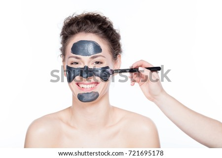 Young beautiful woman is having a black charcoal mask applied on her skin. Skincare.