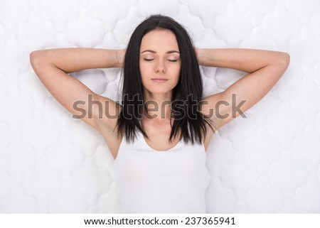 Young, beautiful woman is lying on the bed. Quality mattress.