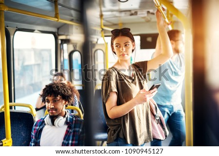 Young beautiful woman is standing in the bus using phone and holding onto the bar while waiting to arrive at her destination.