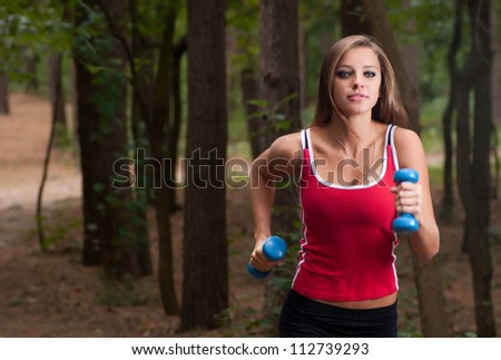 Young beautiful woman jogging in summer park