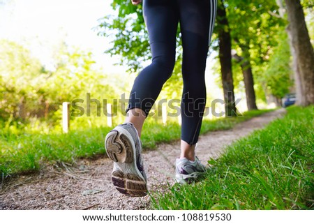 Young beautiful  woman jogging in summer park. Woman in sport outdoors health concept