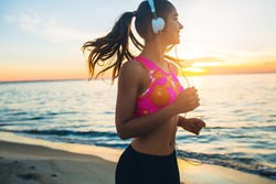 young beautiful woman jogging on beach, morning, fitness outfit, listening to music on headphones, smartphone, sea sunrise, skinny perfect slim body, healthy living lifestyle, summer, smiling, happy