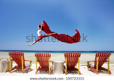 Young beautiful woman jumping at beautiful tropical beach