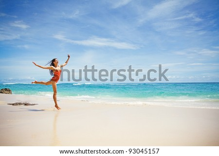 Young beautiful woman jumping over the sand near ocean, Bali, Indonesia