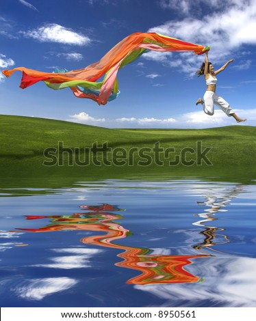 Young beautiful woman jumping with a scarf (reflection made in PS)