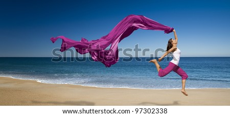 Young beautiful woman jumping with a violet tissure in the beach