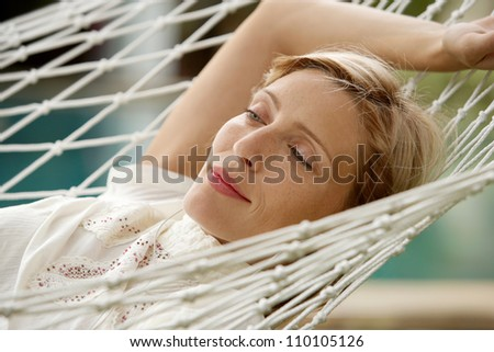 Young beautiful woman laying down on a hammock while on vacations in a tropical destination hotel, outdoors by the swimming pool and listening to music with her earphones.