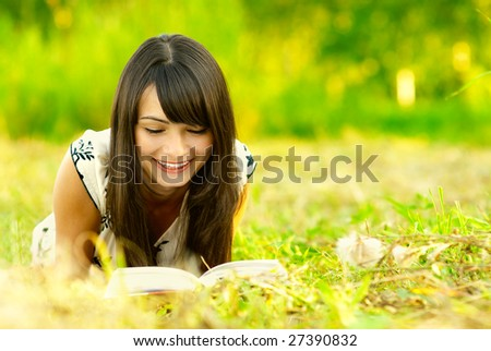 Young beautiful woman lays on green field and reads book. - stock photo