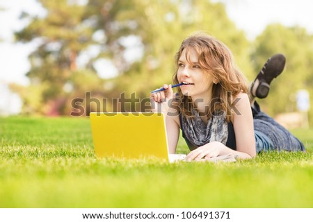 Young beautiful woman lies on green summer meadow with laptop