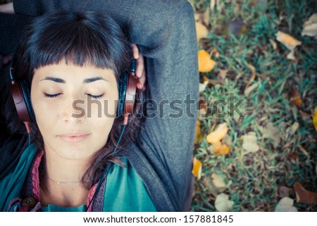 young beautiful woman listening to music at the park in autumn