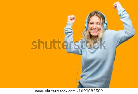 Young beautiful woman listening to music happy and excited celebrating victory expressing big success, power, energy and positive emotions. Celebrates new job joyful #1090083509