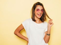 Young beautiful woman looking at camera. In casual summer white T-shirt and jeans shorts in round sunglasses. Positive female shows facial emotions. Funny model isolated on yellow