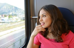 Young beautiful woman looking through the train window. Happy train passenger traveling sitting in a seat and looking through the window.