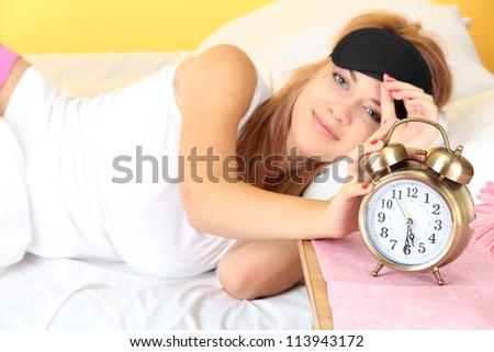 young beautiful woman lying on bed with eye mask and  alarm clock, on yellow background