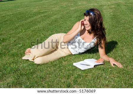 Young beautiful woman lying on grass and speaking on the telephone