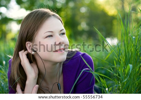 young beautiful woman lying on the grass and listening music