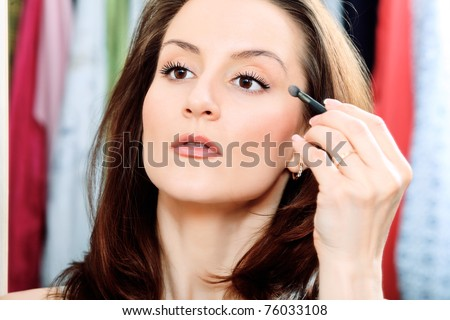Young beautiful woman making up at home.